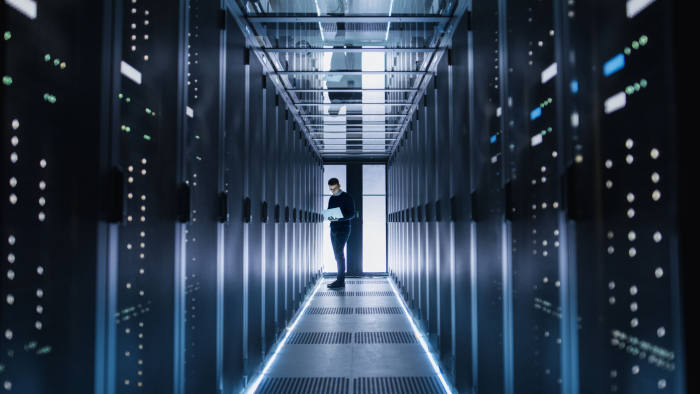 Male IT Engineer Works on a Laptop in a Big Data Center. Rows of Rack Servers are Seen.; Shutterstock ID 662878942; Department: -; Job/Project: -; Employee Name: -