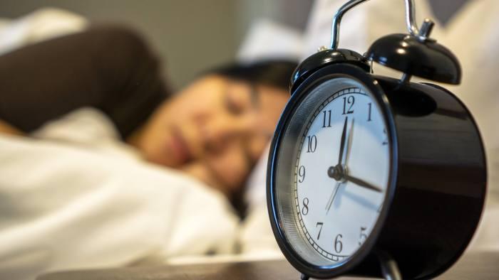 girl sleeping on bed,alarm clock at bedside
