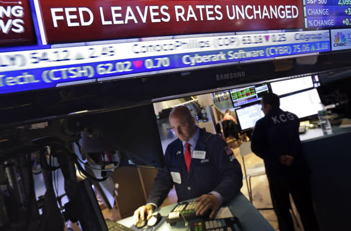 FILE - In this June 17, 2015, file photo, a television screen at the trading post of specialist John Parisi, left, shows the decision of the Federal Reserve, on the floor of the New York Stock Exchange. In December 2008, at the height of the financial crisis, the Fed cut its benchmark rate, called the federal funds rate, to a record-low range between zero and 0.25 percent. The goal was to reduce loan rates for companies and individuals as much as possible to spur borrowing and spending and thereby help stimulate the economy. (AP Photo/Richard Drew, File)