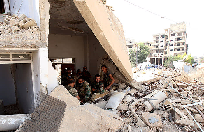 Syrian army soldiers gather at the entrance of a damaged building in the government-controlled part of the besieged town of Daraya on August 26, 2016, as thousands of rebel fighters and civilians prepared to evacuate under an accord struck a day earlier. An estimated 8,000 people remain in the town, despite a government siege lasting four years and regular regime bombardment. / AFP / Youssef KARWASHAN (Photo credit should read YOUSSEF KARWASHAN/AFP/Getty Images)
