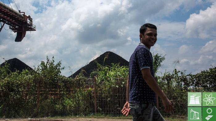 SAMARINDA, INDONESIA - AUGUST 26:  A man walks past a coal stock pile on August 26, 2016 outside Samarinda, East Kalimantan.  Indonesia's East Kalimantan was reported to be one of the worst affected province when coal prices dropped from a high of over USD 127.05 per metric ton in 2011 to the current price of around USD 50 per metric ton in August 2016. Commodity-rich towns in Kalimantan, the world's largest exporter of thermal coal, were hit hard when coal mining companies ceased operations which created a lack of job opportunities and severe social implications, such as an increase in drug abuse and prostitution, as miners found difficulties in finding job opportunities. As the number of unemployment rises in coal mines at parts of Indonesia, both foreign and local workers return home leaving some villages with 50 percent less population leaving abandoned housing and infrastructures while construction sites have been left delayed or cancelled. (Photo by Ed Wray/Getty Images)