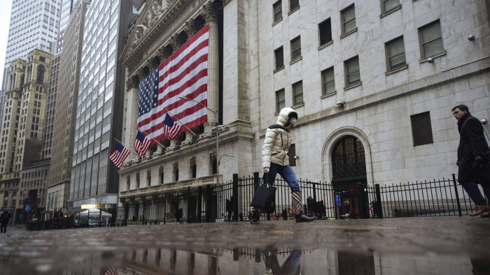 A pedestrian wearing a surgical mask and gloves walks past the New York Stock Exchange on Thursday, March 19, 2020, in New York. Stocks are swinging between gains and losses in early trading on Wall Street Thursday, but the moves are more subdued than the wild jabs that have dominated recent weeks. At least for now. (AP Photo/Kevin Hagen)