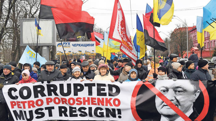 People hold a banner depicting the crossed out Ukrainian President Petro Poroshenko and with the signing reading