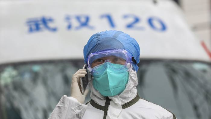 In this Sunday, Jan. 26, 2020 photo, a nurse in protective gear talks on her phone near an ambulance in Wuhan in central China's Hubei Province. A new viral illness being watched with a wary eye around the globe accelerated its spread in China on Sunday with 56 deaths so far, while the U.S. Consulate in the city at the epicenter announced it will evacuate its personnel and some private citizens aboard a charter flight. (Chinatopix via AP)