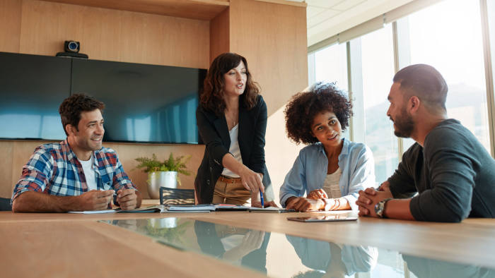 Young businesswoman discussing something with her coworkers while standing at the conference table. Multi ethnic business team meeting in office.