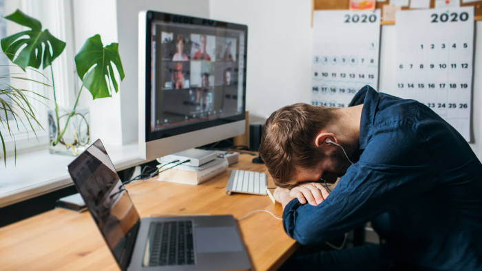 Riga, Latvia - March 28 2020: Tired businessman sleeping on his work desk while having a video call via a computer in the home office. Remote team meeting video online conference Exhausting Calls; Shutterstock ID 1705987216; Department: -; Job/Project: -; Employee Name: -