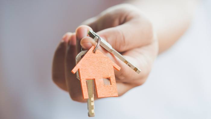 Female hand holding keys with house key,real estate agent.