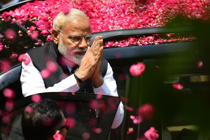 Indian Prime Minister and leader of the Bharatiya Janata Party (BJP) Narendra Modi gestures to supporters as he arrives to file his election nomination papers at district collectorate office, in Varanasi on April 26, 2019. (Photo by SANJAY KANOJIA / AFP) (Photo credit should read SANJAY KANOJIA/AFP/Getty Images)