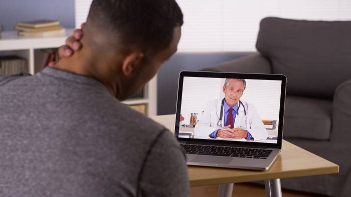 Black patient discussing health problems with doctor online