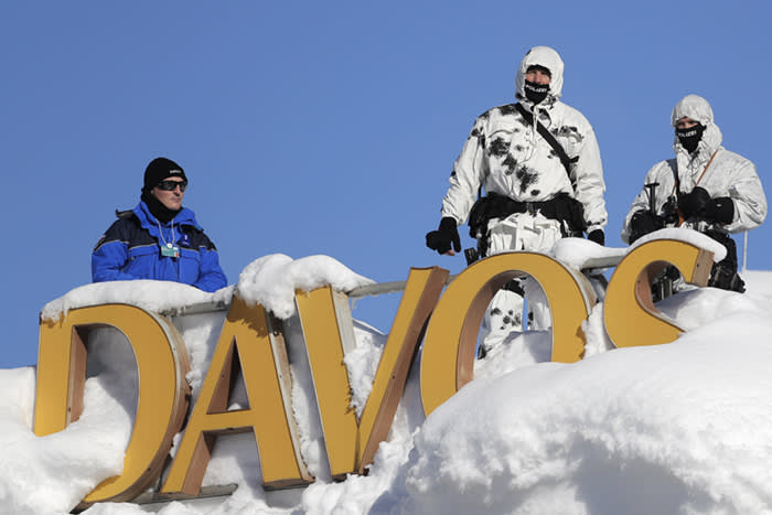 Armed Swiss police officers stand guard on the roof of a hotel near the congress center where the annual meeting of the World Economic Forum takes place in Davos, Switzerland, Tuesday, Jan. 23, 2018. (AP Photo/Markus Schreiber)