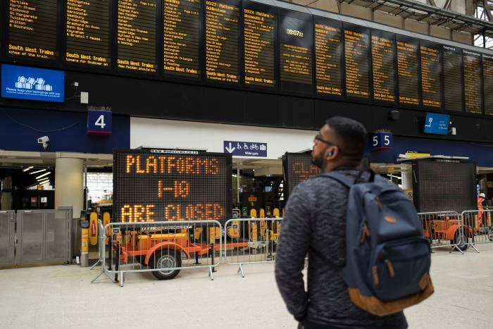 A commuter passes signs alerting passengers to the closure of platforms 1-10 at London Waterloo rail station in central London on August 7, 2017, as Network Rail commences major work to upgrade the station's platforms. The work, which is planned to run until August 28, is expected to extend the platforms, allowing longer trains to operate, which will provide space for more passengers at peak times, Network Rail said. / AFP PHOTO / Tolga Akmen        (Photo credit should read TOLGA AKMEN/AFP/Getty Images)
