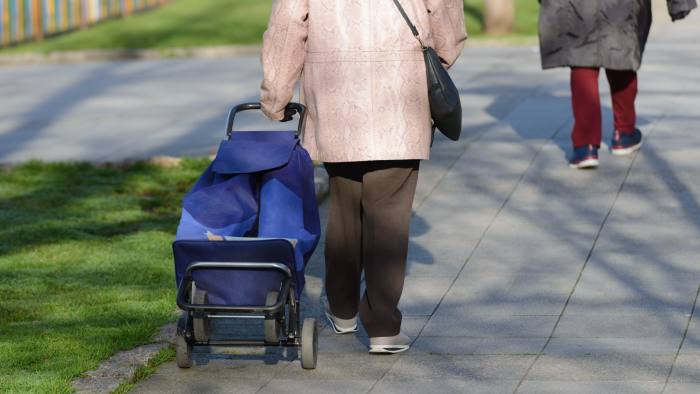 image of elderly woman with a bag on wheels on the street, rear view