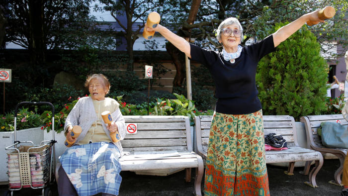 """Natsu Naruse (L), 100 year-old, and other partcipants exercise with wooden dumbbells during a health promotion event to mark Japan's """"Respect for the Aged Day"""" at a temple in Tokyo's Sugamo district, an area popular among the Japanese elderly, Japan, September 18, 2017.   REUTERS/Toru Hanai - RC1C20FDDEC0"""
