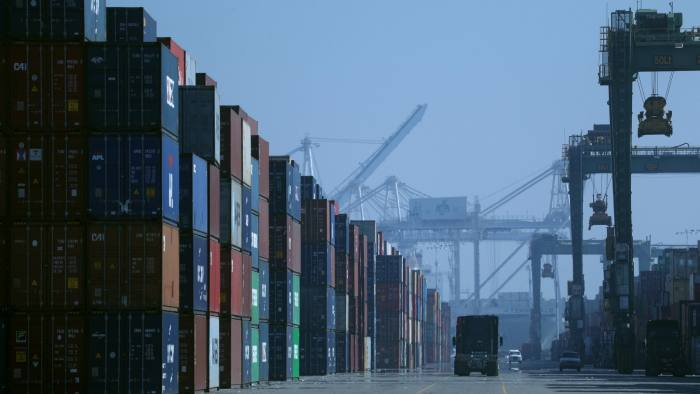 OAKLAND, CALIFORNIA - NOVEMBER 18: A truck drives past stacks of shipping containers at the Port of Oakland on November 18, 2019 in Oakland, California. The World Trade Organization (WTO) says that global flows of goods across borders is on track to fall to the lowest level in ten years as tariffs and trade tensions continue to impact imports and exports. (Photo by Justin Sullivan/Getty Images)