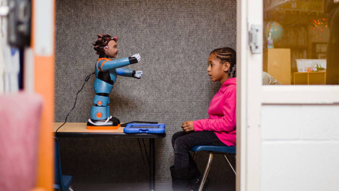 Destiny Ragin, 7, listens intently as Milo, the robot, gives her instructions for an exercise they will do together.