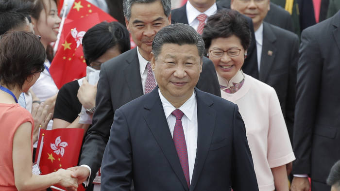 Chinese President Xi Jinping, accompanied by Hong Kong Chief Executive Leung Chun-ying, rear left, and chief executive-elect Carrie Lam, rear right, arrives at Hong Kong's airport, Thursday, June 29, 2017. Hong Kong is planning a big party as it marks 20 years under Chinese rule. But many people in the former British colony are not in the mood to celebrate. Fireworks, a gala variety show and Chinese military displays are among the official events planned to coincide with a visit by Chinese President Xi Jinping starting Thursday for the occasion. (AP Photo/Kin Cheung)