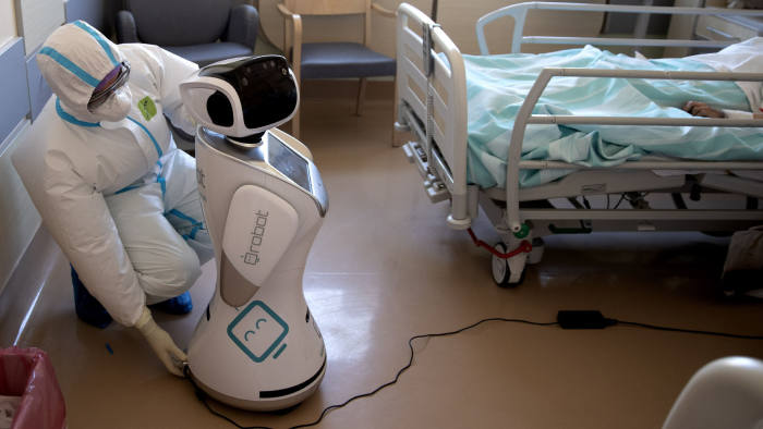 Deputy head of the intensive care unit Flavio Tangian, prepares a robot at 'Ospedale di Circolo' hospital, in Varese, Italy, Wednesday, April 8, 2020. Six robots will help healthcare professionals assist Covid-19 patients, one robot for every two patients to maximize monitoring and assistance. The new coronavirus causes mild or moderate symptoms for most people, but for some, especially older adults and people with existing health problems, it can cause more severe illness or death. (AP Photo/Luca Bruno)