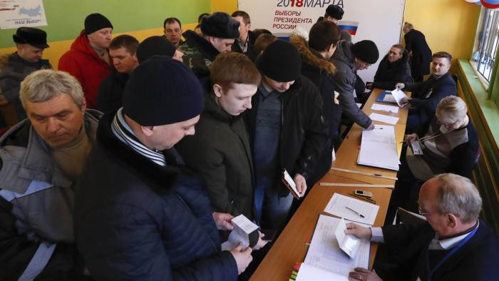 People queue before receiving their ballots and casting their votes at a polling station during the presidential election in Moscow, Russia March 18, 2018. REUTERS/Grigory Dukor