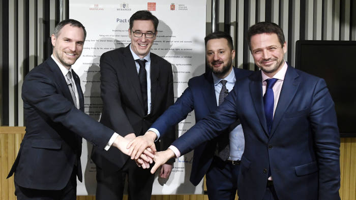 The mayors of the capitals of the Visegrad Four or V4 countries Czech Republic, Hungary, Poland and Slovakia, from left, Zdenek Hrib of Prague, Gergely Karacsony of Budapest, Matus Vallo of Bratislava, and Rafal Trzaskowski of Warsaw pose after they signed the Pact of Free Cities as they announce the establishment of the Alliance of Free Cities of Europe during their meeting in the aditorium of the Central European University in Budapest, Hungary, Monday, Dec. 16, 2019. (Szilard Koszticsak/MTI via AP)