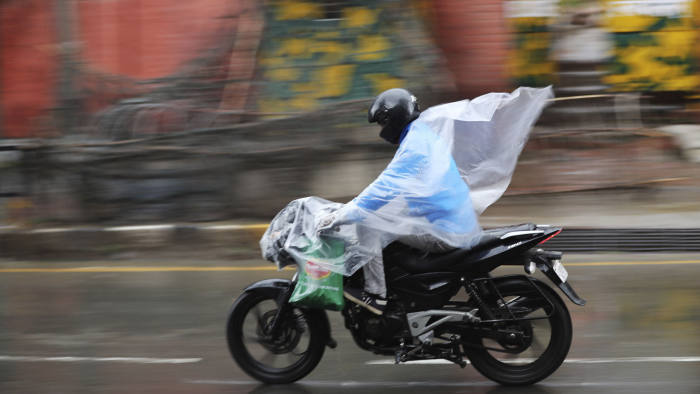 A Kashmiri man drives his motorbike covering himself with a plastic sheet as it rains in Srinagar, Indian controlled Kashmir, Tuesday, March 24, 2020. (AP Photo/Mukhtar Khan)