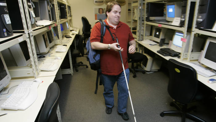 """Microsoft Corp. employee Kelly Ford, a test lead for the Internet Explorer internet browser user experience, walks Monday, Sept. 25, 2006 through the lab in Redmond, Wash. used to test various accessibility features of the Windows operating system as well as third-party accessibility products designed to work with Windows. Ford, who has been blind since birth, was testing a program Monday that provides audible feedback about what is being displayed on a web page and also displays web-page information on a """"braille display"""" that can be read by touch. As part of his job, Ford also manages a team of people who are working to improve web page browsing for all users, not just those with disabilities. (AP Photo/Ted S. Warren)"""