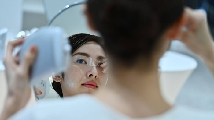 An employee for Japanese cosmetics company Kao uses a palm-sized diffuser on her face, during a product demonstration in Tokyo on December 4, 2019. - Kao on December 4 unveiled what it said was the world's first spray-on skin, using fibres one-100th the thickness of a human hair to form a membrane covering the face. (Photo by CHARLY TRIBALLEAU / AFP) (Photo by CHARLY TRIBALLEAU/AFP via Getty Images)