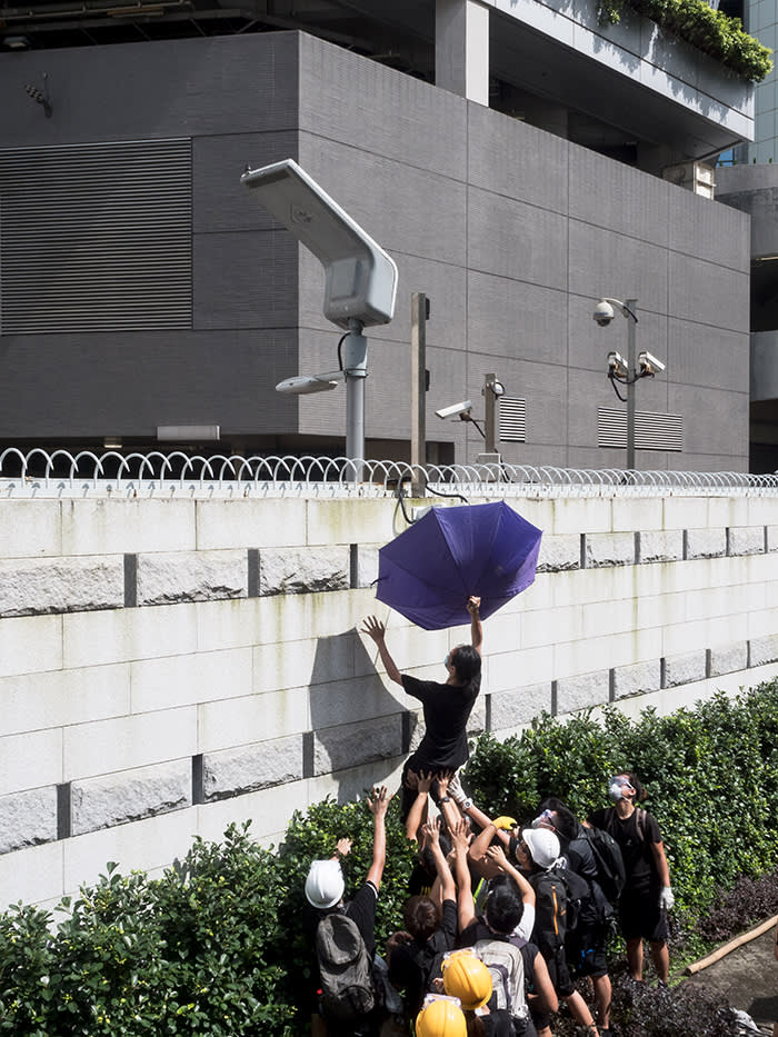 After protesters surround police headquarters in Wan Chai in late June, some attempted to block the CCTV cameras using an umbrella