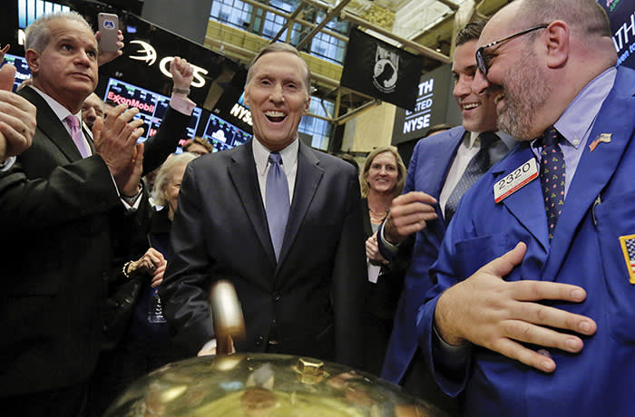 Athene Holding Ltd. Chairman and CEO Jim Belardi, center, is applauded as he rings a ceremonial bell to mark the beginning of trades in his company's IPO, on the floor of the New York Stock Exchange, Friday, Dec. 9, 2016. (AP Photo/Richard Drew)