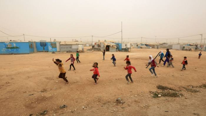 epa06326962 Syrian refugee children play in a dusty wind day, on the inauguration day of the largest ever built solar plant in a refugee camp in the world, at Zaatari refugee camp, Jordan, 13 November 2017. The 12.9 megawatts plant was funded by the Government of Germany through the KfW Development Bank. The 15 million Euros project is expected to allow the United Nations High Commissioner for Refugees (UNHCR) to bring affordable and sustainable energy to some 80,000 Syrian refugees and its host community. EPA-EFE/STRINGER