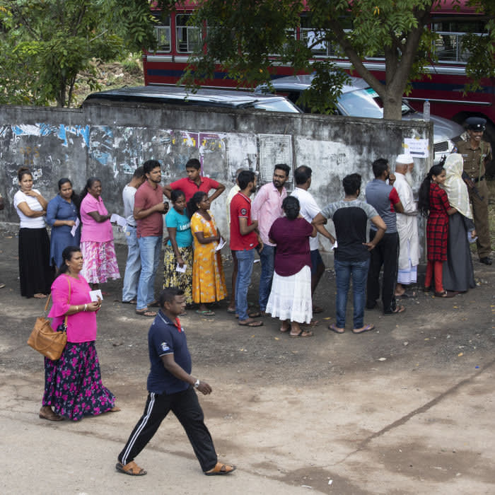 COLOMBO - NOVEMBER 16: Sri Lankan people wait in line to vote on Saturday to elect a new President in Colombo, Sri Lanka on November 16, 2019. In the early morning gunmen opened fire on a bus carrying Muslim voters, no injuries were reported in the incident before polls opened. The country is still recovering from the April, Easter Sunday bombings that killed 250 people. This election is seen as a test of the future stability of the country in a tight race with front runners Gotabaya Rajapaksa and Sajith Premadasa. (Photo by Paula Bronstein/Getty Images)