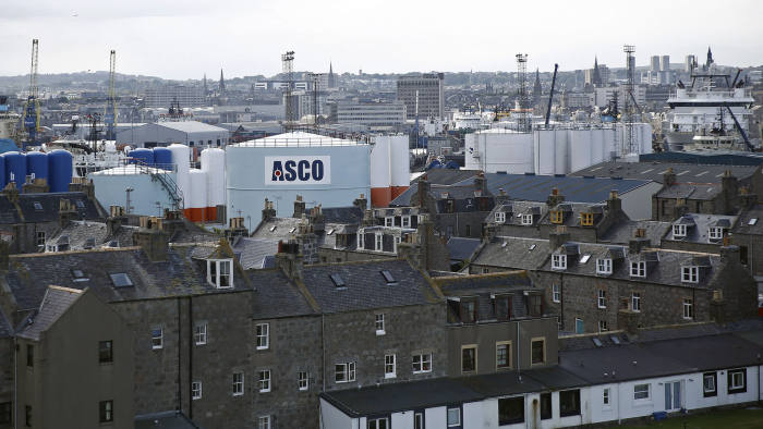 Oil Rig Support Vessels And Port Operations At Aberdeen Harbor...An ASCO Group Ltd. logo sits on a fuel storage silo beyond residential properties near Aberdeen Harbour, operated by the Aberdeen Harbour Board, in Aberdeen, U.K., on Friday, Aug. 8, 2014. The oil and gas industry remains central to the debate on Scotland's independence ahead of the forthcoming Sept. 18 referendum. Photographer: Simon Dawson/Bloomberg
