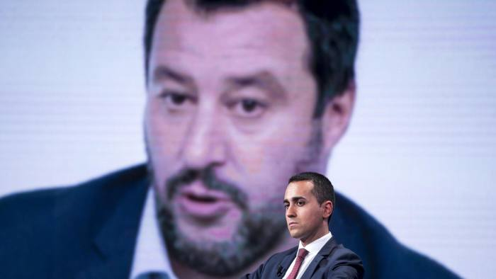 Mandatory Credit: Photo by ANGELO CARCONI/EPA-EFE/REX/Shutterstock (9936385i) Italian Deputy Premier and Labour and Industry Minister, Luigi Di Maio, sits next to a large image of Italy's interior minister Matteo Salvini on a screen, as he attends the Raiuno Italian program 'Porta a porta' conducted by Italian journalist Bruno Vespa, in Rome, Italy, 17 October 2018. Italian Deputy Premier, Luigi Di Maio on 'Porta a porta', Rome, Italy - 17 Oct 2018