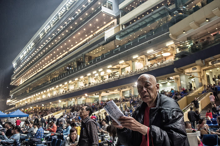 In this picture taken on March 31, 2016, spectators attend the night horse races at the Hong Kong Jockey Club in the Happy Valley district of Hong Kong. Hong Kong has two racecourses, Happy Valley and Sha Tin, with meets on Wednesday and Sundays drawing hardcore enthusiasts glued to form guides, and casual visitors more interested in a cold beer than the horses. / AFP / Anthony WALLACE / To go with AFP story: Hong Kong-racing-economy, FEATURE by Dennis Chong (Photo credit should read ANTHONY WALLACE/AFP/Getty Images)