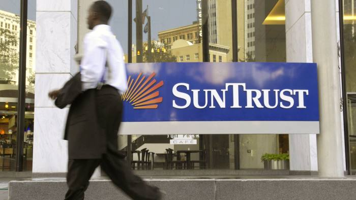 A Pedestrian walks by the headquarters of SunTrust Banks Inc. in Atlanta, Georgia, on Monday Aug. 20, 2007. SunTrust Banks Inc., seeking to cut $530 million in annual costs by 2009, expects to eliminate about 7 percent of its workforce by the end of next year as profit from retail and commercial banking declines. Photographer: Chris Rank/ Bloomberg News.