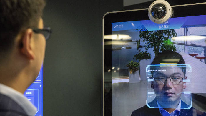 Xu Li, chief executive officer of SenseTime Group Ltd., is identified by the company's facial recognitionsystem on a screen as he poses for a photograph at SenseTime's showroom in Beijing, China, on Friday, June 15, 2018. SenseTime's image-identifying algorithms have made it the world's most valuable AI startup and an early leader in China, where it's won contracts with the country's top phonemakers, largest telecommunications company, and biggest retailer. Photographer: Gilles Sabrie/Bloomberg