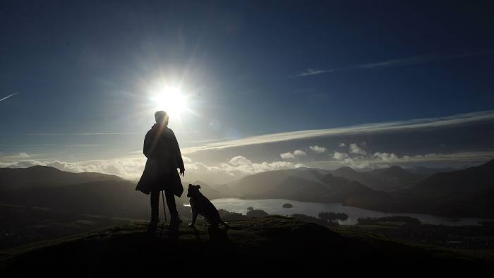 KESWICK, ENGLAND - DECEMBER 04:  A fell walker enjoys the panoramic views from on top of Latrigg in the Lakeland Fells on December 4, 2009 in Keswick, England. After being cut off by the recent devastating floods in Cumbria, tourists and visitors are returning to enjoy it's vistas and national park countryside.  (Photo by Christopher Furlong/Getty Images)