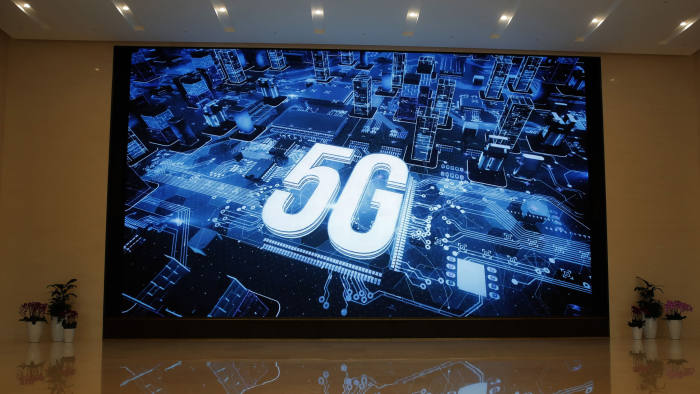 In this March 6, 2019, photo, a 5G logo is displayed on a screen outside the showroom at Huawei campus in Shenzhen city, China's Guangdong province. Australia's ban on Chinese telecoms giant Huawei's involvement in its future 5G networks and its crackdown on foreign covert interference are testing Beijing's efforts to project its power overseas. In its latest maneuver, China sent three scholars to spell out in interviews with Australian media and other appearances steps to mend the deepening rift with Beijing - a move that appears to have fallen flat. (AP Photo/Kin Cheung, File)
