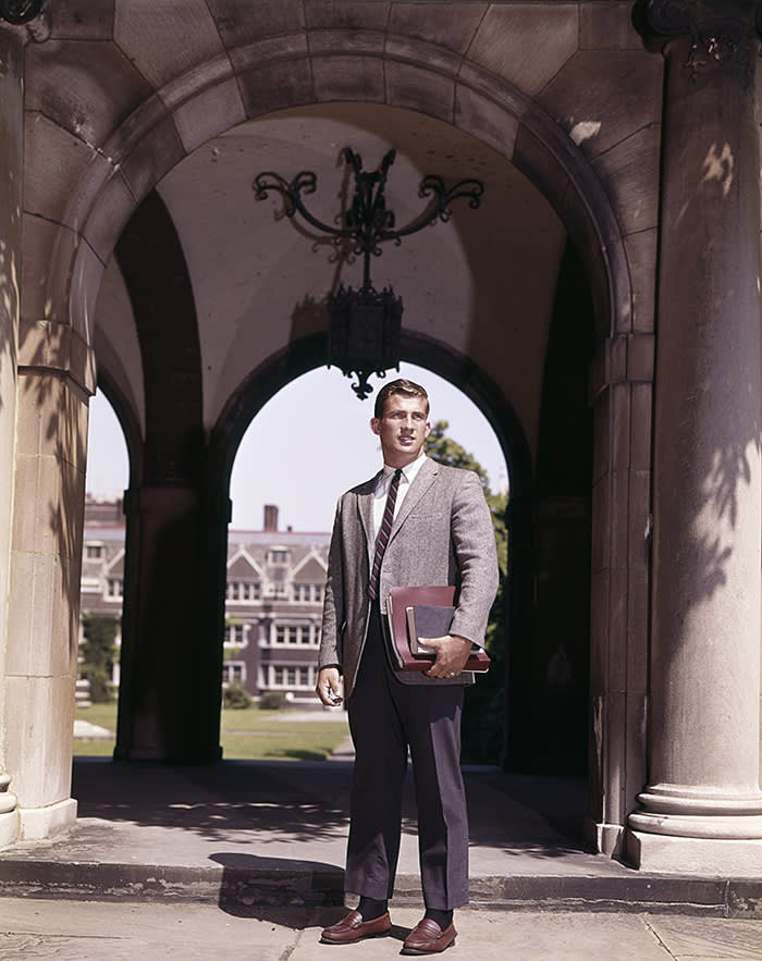 1960s MAN COLLEGE STUDENT STANDING NEAR ARCH LEADING TO COLLEGE CAMPUS QUADRANGLE (Photo by H. Armstrong Roberts/ClassicStock/Getty Images)
