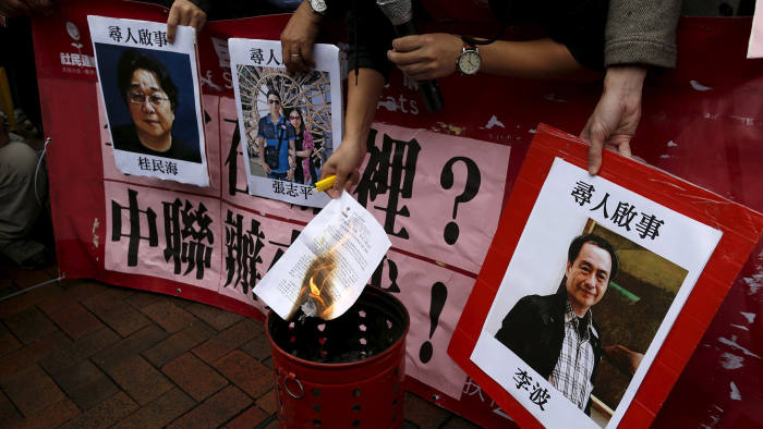 A pro-democracy demonstrator burns a letter next to pictures of missing staff members of a publishing house and a bookstore during a protest to call for an investigation behind their disappearance, outside the Chinese liaison office in Hong Kong...A pro-democracy demonstrator burns a letter next to pictures of missing staff members of a publishing house and a bookstore, including Gui Minhai, a China-born Swedish national who is the owner of Mighty Current, Cheung Jiping, the business manager of the publishing house and Causeway Bay Books shareholder Lee Bo (L-R), during a protest to call for an investigation behind their disappearance, outside the Chinese liaison office in Hong Kong, China January 3, 2016. Hong Kong opposition lawmakers protested on Sunday outside Beijing's representative office in the Chinese-ruled city over the disappearance of a bookseller who specializes in publications critical of the Communist Party government. REUTERS/Tyrone Siu