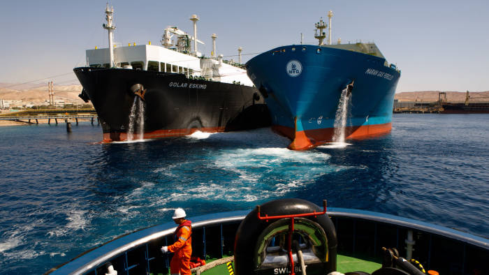Bloomberg Best of the Year 2018: A crew member aboard the emergency standby ASD tug boat 'Tareq 3' watches as the 'Golar Eskimo' Floating Storage and Regasification Unit (FRSU), center right, takes on liquefied natural gas (LNG) from the 'Maran Gas Pericles' tanker at Aqaba port, operated by Aqaba Development Corp., in Aqaba, Jordan, on Wednesday, April 11, 2018. Photographer: Annie Sakkab/Bloomberg