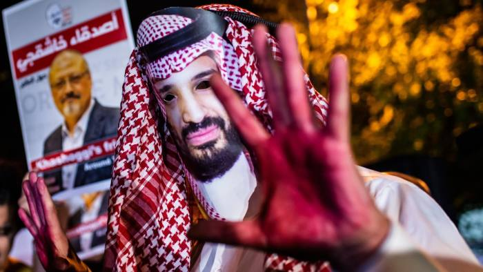 A protestor wears a mask of depicting Saudi Crown Prince Mohammad Bin Salman with red painted hands next to people holding posters of Saudi journalist Jamal Khashoggi during the demonstration outside the Saudi Arabia consulate in Istanbul, on October 25, 2018. - Jamal Khashoggi, a Washington Post contributor, was killed on October 2, 2018 after a visit to the Saudi consulate in Istanbul to obtain paperwork before marrying his Turkish fiancee. (Photo by Yasin AKGUL / AFP)YASIN AKGUL/AFP/Getty Images