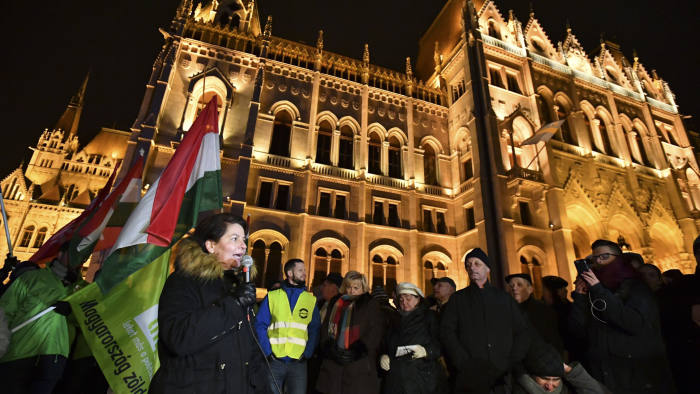 Andrea Varga Damm, lawmaker of the Hungarian oppositional party Jobbik, left, speaks to demonstrators gathered on the Kossuth Square in front of the Hungarian Parliament building during an anti-goverment demonstration in Budapest, Hungary, Friday, Dec.14, 2018. (Marton Monus/MTI via AP)