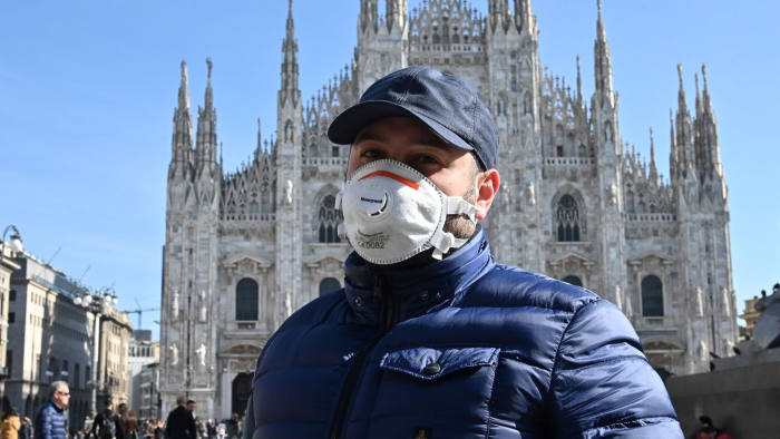 A man wearing a protective facemask walks across the Piazza del Duomo, in front of the Duomo, in central Milan, on February 24, 2020 closed following security measures taken in northern Italy against the COVID-19 the novel coronavirus. - Italy reported on February 24, 2020 its fourth death from the new coronavirus, an 84-year old man in the northern Lombardy region, as the number of people contracting the virus continued to mount. (Photo by Andreas SOLARO / AFP) (Photo by ANDREAS SOLARO/AFP via Getty Images)
