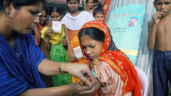 Dhaka, BANGLADESH:  A Bangladeshi woman receives a vaccination from a health worker at a slum during the second phase of the Neonatal Tetanus Elimination (NTE ) campaign, in Dhaka, 05 November 2006.  Bangladesh launched a campaign to vaccinate three millon women against tetanus 05 November in a bid to completely eliminate the disease from the impoverished country by 2007, an official said.  AFP PHOTO/ Shafiq ALAM  (Photo credit should read SHAFIQ ALAM/AFP/Getty Images)