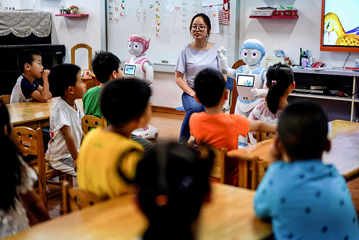 An iPal couple social robot help teach children at a kindergarten in Suzhou, Jiangsu province, China July 4, 2018. Designed to offer education, care and companionship to children and the elderly, the 3.5-feet tall humanoid robots come in two genders and can tell stories, take photos and deliver educational or promotional content. Picture taken July 4, 2018. REUTERS/Aly Song - RC1D7152B5A0