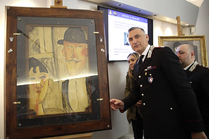 Carabinieri Lieutenant Colonel Nicola Candido stands by a painting attributed to 20th century Italian paints Amedeo Modigliani determined by carabinieri as a fake, during a press conference announcing the conclusion of the preliminary phase of an investigation of 21 paintings seized by Carabinieri during an exhibition in 2017, 15 of which attributed to Modigliani, in central Rome, Wednesday, March 13, 2019. (AP Photo/Alessandra Tarantino)