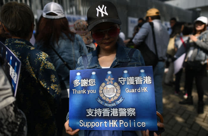 """A supporter of the Hong Kong Police Force holds a placard while participating in a pro-law enforcement rally outside the Legislative Council building in Hong Kong on November 16, 2019. - China's President Xi Jinping warned November 14 that protests in Hong Kong threaten the """"one country, two systems"""" principle governing the semi-autonomous city that has tipped into worsening violence with two dead in a week. (Photo by Ye Aung THU / AFP) (Photo by YE AUNG THU/AFP via Getty Images)"""