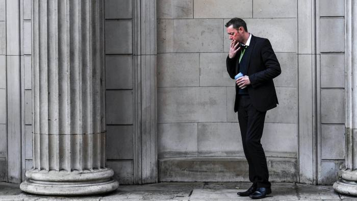 A man smokes outside the Bank of England in the City of London, Britain, December 12, 2017. REUTERS/Clodagh Kilcoyne - RC15C518C7A0