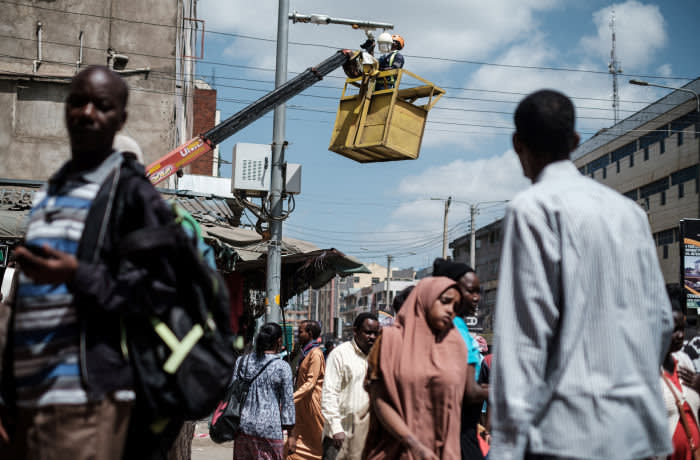 A worker cleans a surveillance camera on a street in Nairobi, on January 18, 2019. (Photo by Yasuyoshi CHIBA / AFP) (Photo credit should read YASUYOSHI CHIBA/AFP via Getty Images)