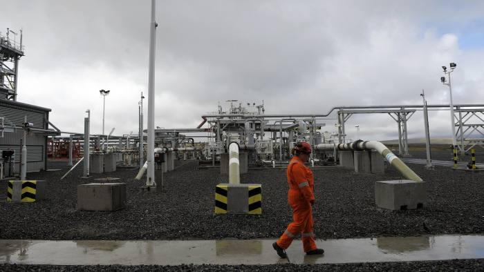 """A worker walks past pipelines at the Shetland Gas Plant on May 16, 2016 in the Shetlands.  Total officially launched a huge new gas project in Britain's remote Shetland Islands today, hailed by London as a """"vote of confidence"""" in the flagging North Sea oil and gas industry. The French energy giant officially opened the Shetland Gas Plant in Britain's northernmost outpost, which cost £3.5 billion ($5 billion, 4.4 billion euros) to build.  / AFP / Digital / Andy Buchanan        (Photo credit should read ANDY BUCHANAN/AFP/Getty Images)"""
